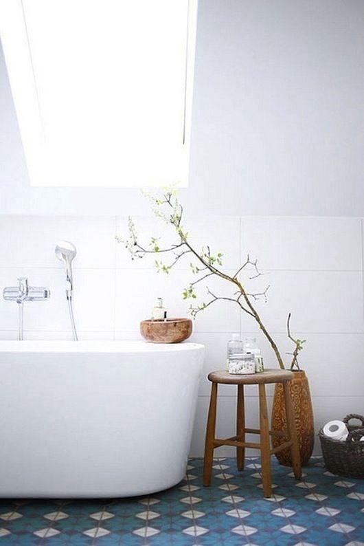 Un sol aux motifs anciens avec une baignoire moderne